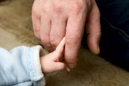 The small child keeping for a finger of the father Stock Photo - 810091