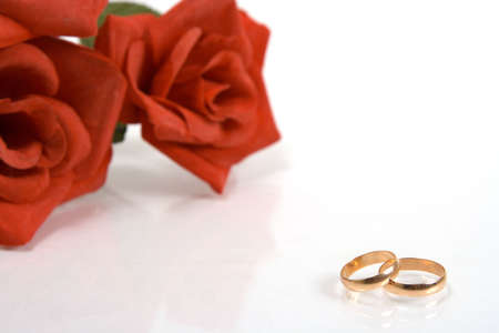 Two wedding rings and red rose at the background photo