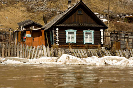 Old house on coast of the spread river photo