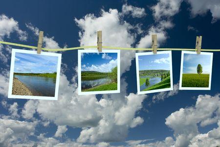 Landscape photographs hanging on a clothesline against a cloudscape Stock Photo - 3242867