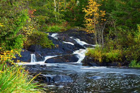 the rocky: mountain waterfall. fast stream water. autumn landscape