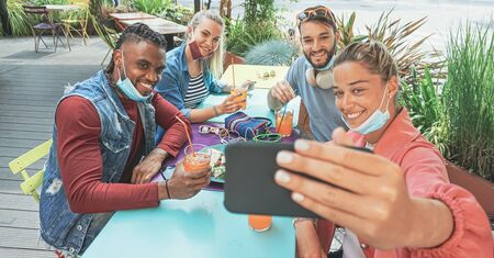Friends taking selfie in a bar restaurant with face mask on in coronavirus time - Young people having fun with drinks and snacks outside with new rules after virus break