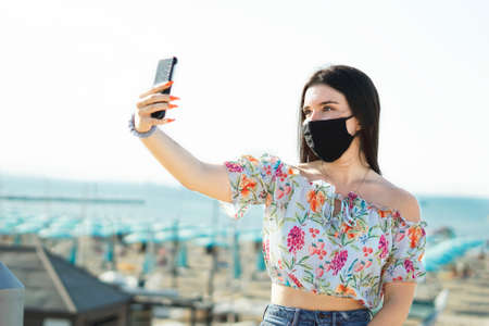Portrait of a pretty girl taking a selfie with face mask in covid-19 time