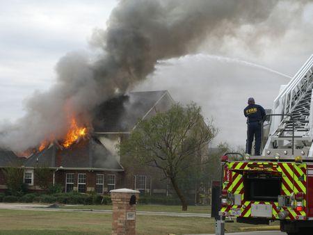 Brandweerlieden die reageren op huis brand  Stockfoto