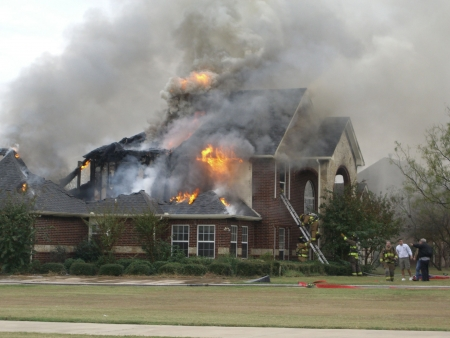 damages: Firemaen responding to house fire Stock Photo