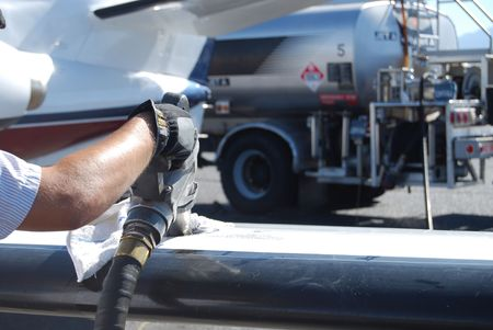 fuel economy: Fuel nozzle in wing filling up aircraft Stock Photo