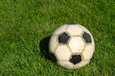 Worn out soccer ball on the pitch grass. Stock Photo