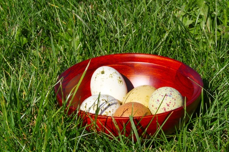 Painted easter eggs in a wooden bowl on the green grass background