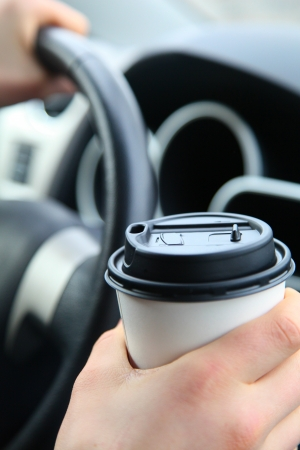 Hand holding white coffee cup on the steering wheel background. Shallow Focus Archivio Fotografico