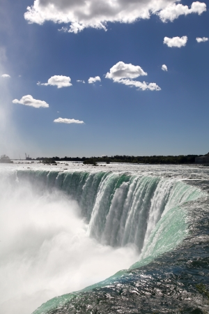 The view of the waterfall on the blue sky background. Niagara Falls, Ontario photo
