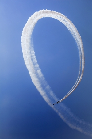 acrobatic: The view of the jet plane smoke tail on the blue sky background