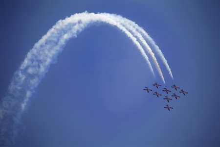 The view of several jet plane in formation. White smoke tail on the blue sky background.