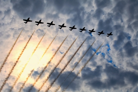 The view of several jet planes in formation on the cloudy sky background.