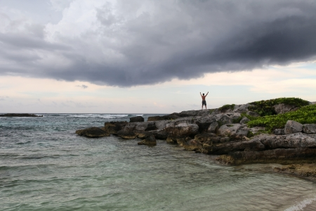 Man raising his hands up staying on the rock on the cloudy sky and sea background Stock Photo