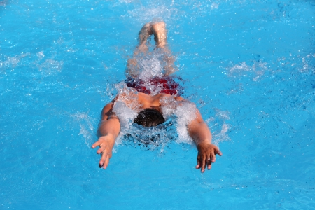 Close-up shot of a young male swimmer, butterfly stroke, shallow focus