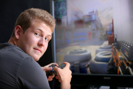 Young man palying video game in front of display, shallow focus