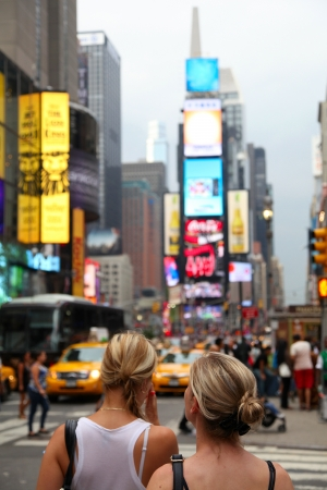 Two girls on the blured Times  Square background, shallow focus Stock Photo