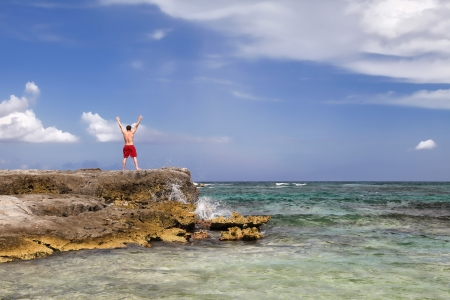 Man raising his hands up staying on the rock on the blue sky and sea background
