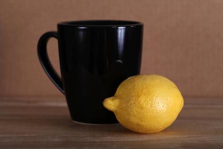 Yellow fresh whole lemon and black coffee mug and yellow lemon still life, shallow focus