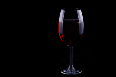 Red wine glass on the black background, shallow focus