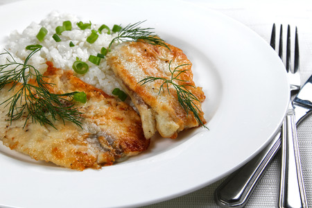 Fried fish with rice on the white plate, shallow focus