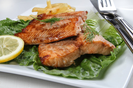 Cooked salmon file on a white plate, shallow focus Stock Photo