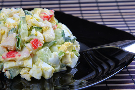Egg and crab meat salad on a black plate, shallow focus Stock Photo