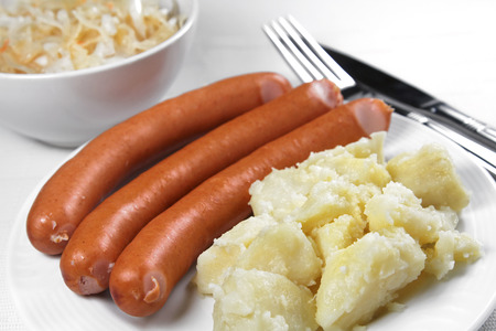 Cooked sausages with potatos and pickled cabbage, shallow focus