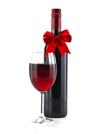 Red wine with Christmas ribbon isolated on white background, shallow focus