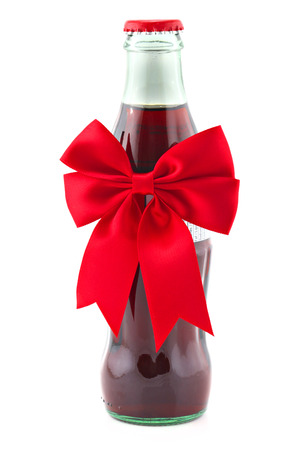 Bottle of non-alchohol drink with christmas ribbon isolated on white, shallow focus