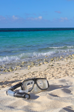 Snorkel and mask on the beach sand on the seasky background, shallow focus Stock Photo