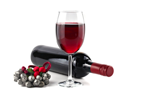 Red wine with Christmas ornament isolated on white background, shallow focus