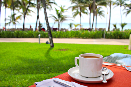 Cup of coffee served in the beach restaurant, shallow focus