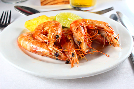 Grilled shrimp served on a white plate, shallow focus
