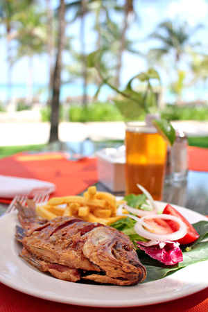 Grilled fish with vegetables served in beach restaurant, shallow focus