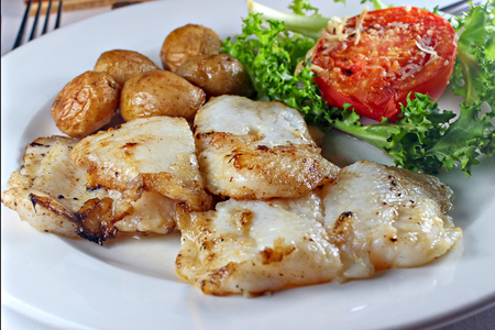 Grilled fish steak with vegetables, shallow focus Stock Photo