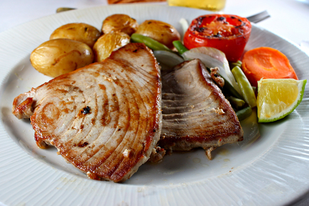 Grilled tuna steak with vegetables, shallow focus