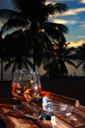 A glass of rum and cigar on the dark palm and sea background, shallow focus