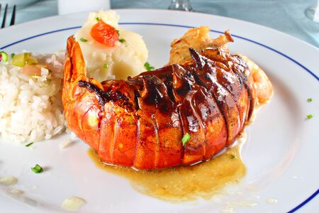 Grilled lobster served with rice and potato, shallow focus