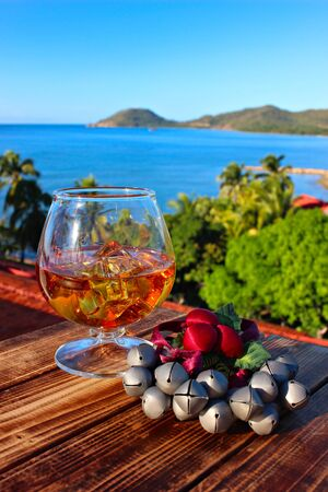 A glass of the rum and christmass ornament on the sea background, shallow focus