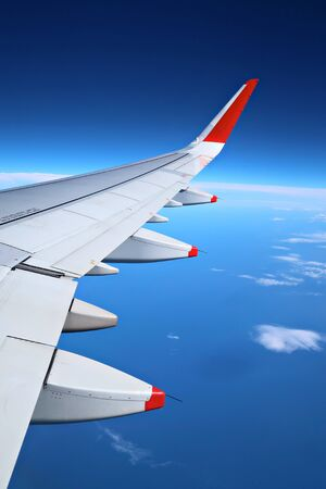 Airplane wing over the sky background, view from window