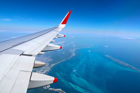 Airplane wing over the sky and ocean background, view from window