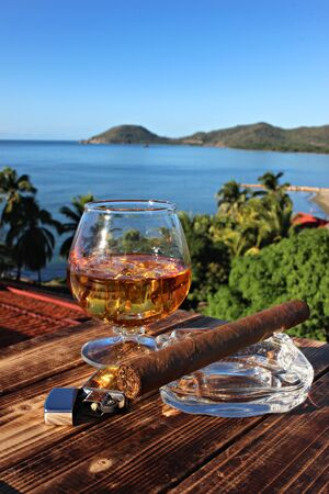A glass of rum and cigar on the sea background, shallow focus