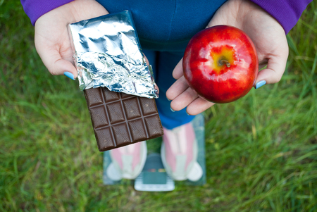 Fat woman wants to lose weight diet top view in blue suit stands on transparent glass scales in pink sneakers on green grass selects big red apple or chocolate bar in foil chocolates Stock Photo