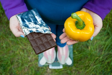 Fat woman wants to lose weight diet top view in blue suit stands on transparent glass scales in pink sneakers on green grass selects large yellow sweet pepper or chocolate bar in foil chocolates
