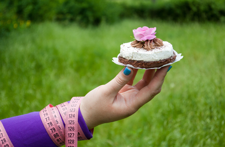 Lose weight fat woman close up of the right hand holding a cake white with a pink rose napkin short nails blue on a background of green grass blurred background pink measuring tape wound on the hand side view Stock Photo