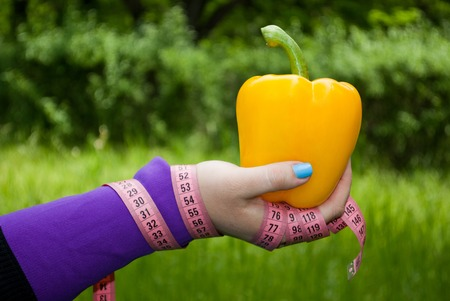 Lose weight fat woman closeup of the right hand holding a big yellow concussion bell pepper short nails blue on a background of green grass blurred background pink measuring tape wound on the hand side view