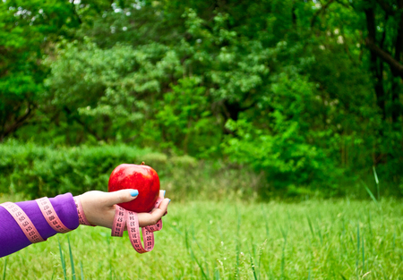 Lose weight fat woman closeup of the right hand holding a large red apple short nails blue on a background of green grass blurred background pink measuring tape wound on the hand side view