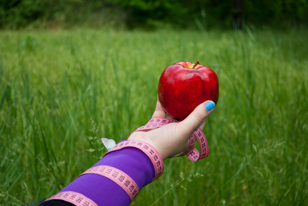 Lose weight fat woman closeup of the right hand holding a large red apple white blue butterfly sits on the hand short nails blue on a background of green grass blurred background pink measuring tape wound on the hand side view Stock Photo