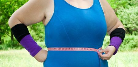 Fat woman wants to lose weight diet view in blue suit on green grass bush tree hands abdomen torso torso chest measurement on the right Stock Photo